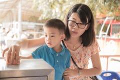 Pojke och hans moder som all toghter donerar vid satta pengar i donationask royaltyfri fotografi