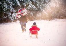 Pojke och hans moder som spelar i vinterlandskap bakgrundsbarnflicka little nätt model lekplats Royaltyfria Bilder
