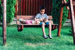 Pojke och hans syster på en gunga Arkivbild