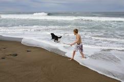 Pojke och hund på kust Arkivfoto