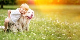 Pojke och hund tillsammans arkivbild