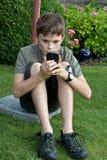 Pojke och mobiltelefon Fotografering för Bildbyråer
