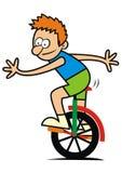 Pojke och monocycle Arkivbild