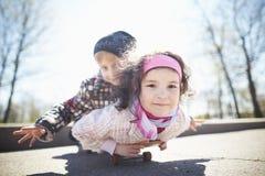Pojke och nätt flicka som skaiting på gatan Royaltyfri Bild
