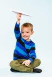 Pojke och pappers- flygplan Arkivfoto