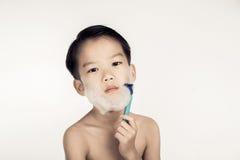 Pojke och rakapparat Arkivbilder