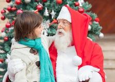 Pojke och Santa Claus Looking At Each Other Fotografering för Bildbyråer