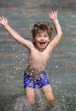 Pojke- och vattendroppar lyckligt hav f?r barn Sommar Havsferie semester Ungen spelar i vattnet Gyckel roligt arkivfoto