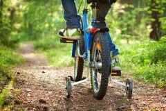 Pojke på cykeln i skogen Arkivbild