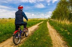 Pojke på cykeln på landsvägen i solig dag Royaltyfri Bild