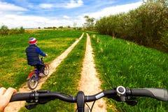 Pojke på cykeln på landsvägen i solig dag Arkivfoto