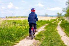 Pojke på cykeln på landsvägen i solig dag Fotografering för Bildbyråer