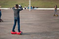 Pojke på en hoverboard som försöker att gå på den med händer på huvudet, förvirrade blickar Royaltyfria Bilder