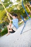 Pojke på en lekplatsgunga Royaltyfri Fotografi