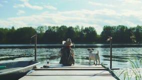 Pojke på en pir med hunden arkivfilmer