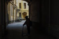 Pojke på en sparkcykel royaltyfria bilder