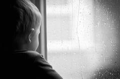 Pojke på fönstret Arkivfoto