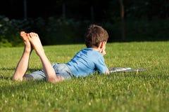 Pojke på gräset Arkivbild