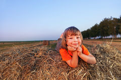 Pojke på höstack i fältet fotografering för bildbyråer