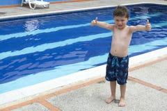 Pojke på kanten av en simbassäng Arkivbild
