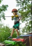 Pojke på klättringaktivitet i hög tråd Forest Park Tabellbergcablewayen lurar på sakkunniga igen fotografering för bildbyråer