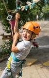 Pojke på klättringaktivitet i hög tråd Forest Park Tabellbergcablewayen lurar på sakkunniga igen royaltyfria bilder