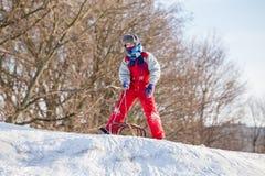 Pojke på pulkan överst av den väntande på ridningen för snöig kulle royaltyfri bild