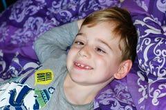 Pojke på säng fotografering för bildbyråer