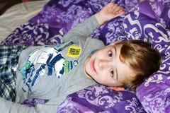 Pojke på säng arkivfoton