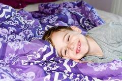 Pojke på säng royaltyfria foton