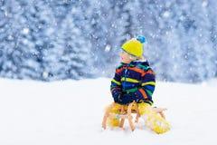 Pojke på släderitt Sledding för barn Unge på pulkan arkivbild
