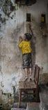 Pojke på stolgatakonst i Penang Arkivfoto