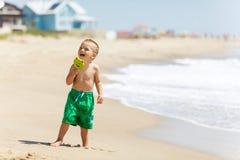 Pojke på stranden med godisen Arkivbild