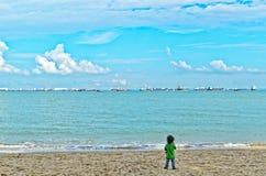Pojke på stranden som ser havet royaltyfria foton