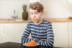 Pojke på tabellen med lång ramsa av strimlade morötter Royaltyfria Foton