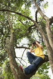 Pojke på trädfilialen som ser till och med kikare arkivbilder