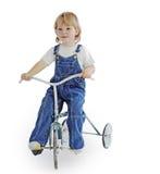 Pojke på trehjulingtappningcykeln Royaltyfri Foto