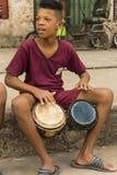 Pojke på trottoaren som spelar bongoshavannacigarr Arkivbilder