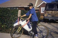 Pojke på cykeln som levererar tidningar Arkivbild