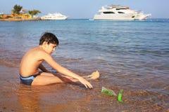 Pojke på leken för badning för strandtagandesol med sand Royaltyfri Fotografi