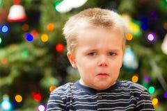Pojke som är olycklig om jul Arkivbild