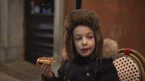 Pojke som äter belgiska dillandear med choklad på gatan lager videofilmer