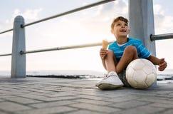 Pojke som äter en glass som sitter nära sjösida Arkivbilder