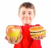 Pojke som äter en hamburgare. arkivfoto