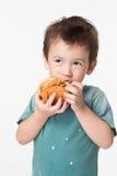 Pojke som äter en hamburgare Royaltyfri Fotografi