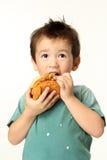 Pojke som äter en hamburgare Arkivbilder