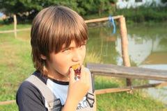 Pojke som äter en plommon Royaltyfria Foton