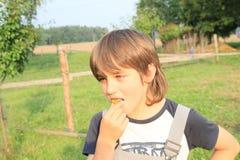 Pojke som äter en plommon Royaltyfria Bilder