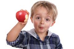 Pojke som äter ett rött äpple arkivbild