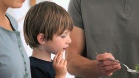 Pojke som äter grönsaker, medan hans fader tjänar som plattorna